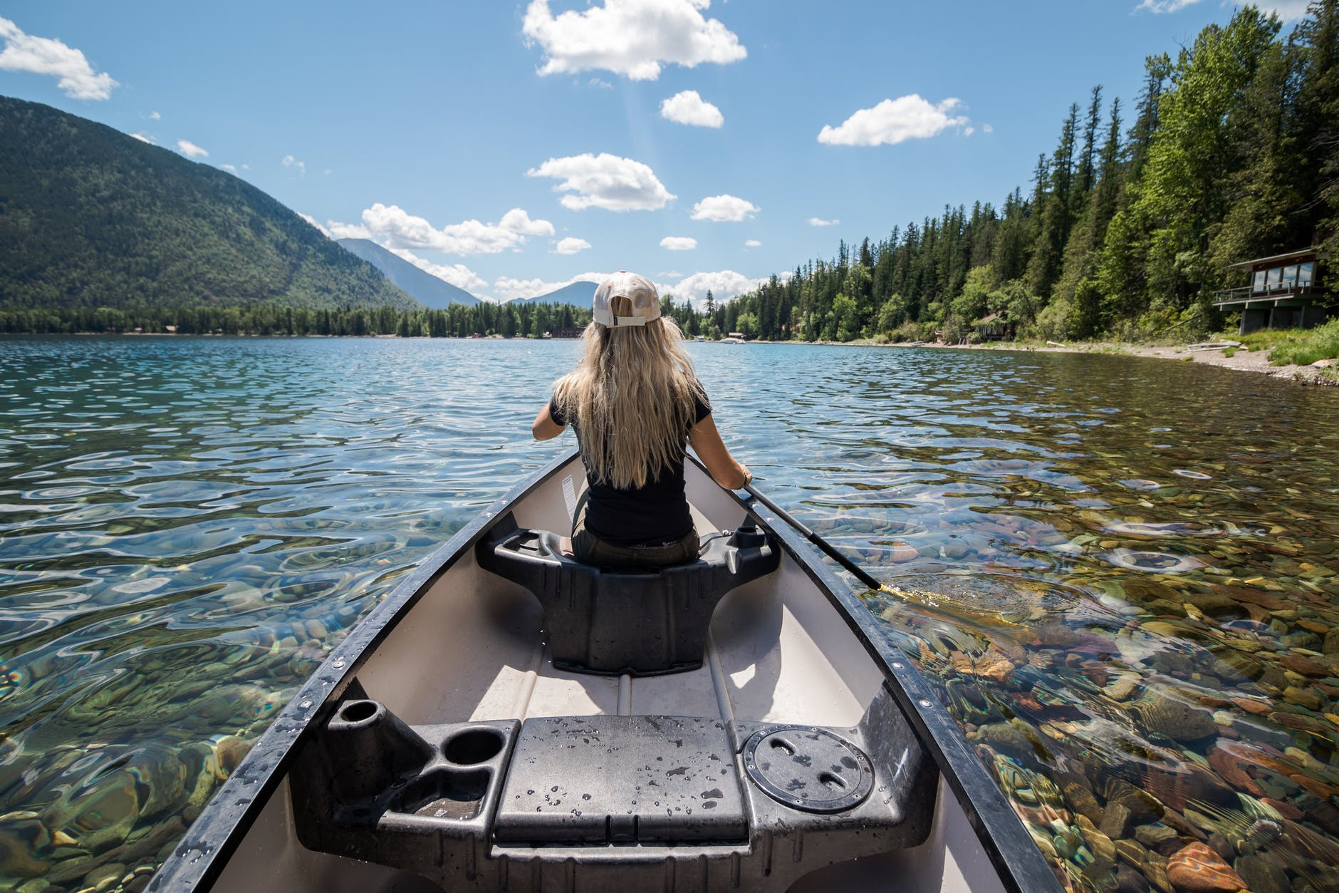 anonymous young lady paddling boat in lake during trip in mountains
